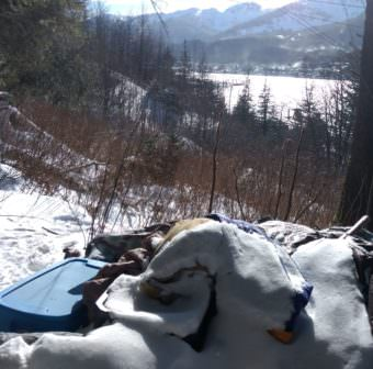 Snow collects on abandoned belongings at a campsite above downtown Juneau on March 3, 2017. AJT Mining Properties evicted its occupants in February. Homeless people have few legal camping options in the winter. (Photo Jacob Resneck/KTOO)