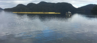 The tugboat Powhatan remains underwater, surrounded by booms to contain the oil spill. (Photo courtesy of SEAPRO)