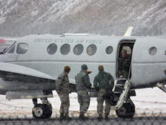 Explosive specialists with the U.S. Air Force return to their plane Tuesday after destroying World War II-era ordnance found in Unalaska. (Photo by Laura Kraegel/KUCB)