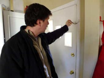 Juneau resident David Noon resets the chain on the back door of his home. When his place was burglarized in October, the chain was not set and the burglar was able to kick in the door because the deadbolt lock did not fully extend into the door jamb. The door, door jamb, and the deadbolt have since been repaired.