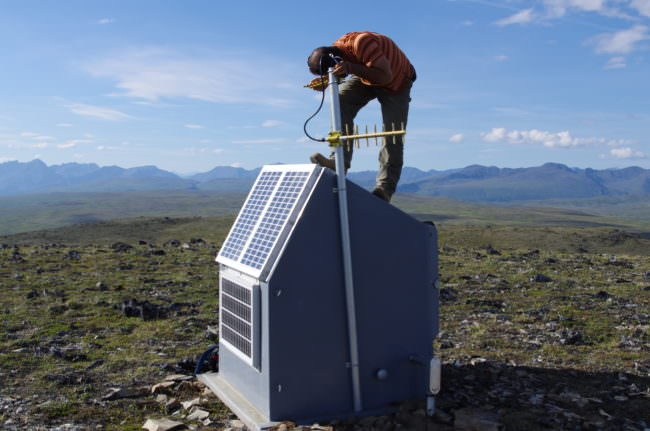 Field engineer Scott Dalton adjusts a radio communications link at a seismic station south of Cantwell.
