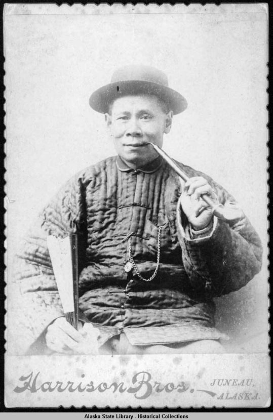 China Joe smokes a pipe and holds a fan in this gold rush era studio portrait.
