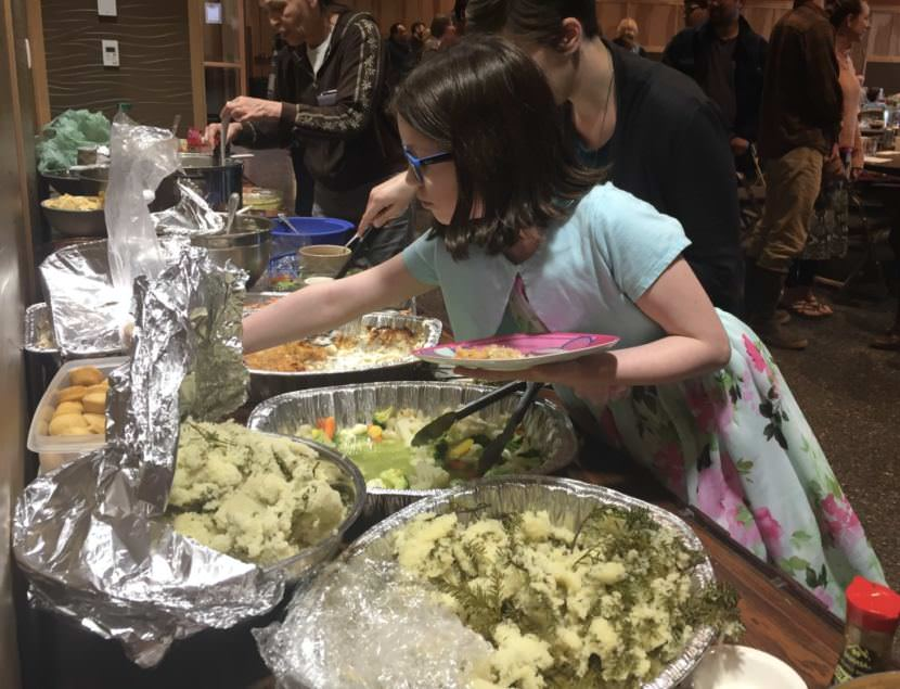 Zoe Trafton piles her plate with herring eggs at Sitka Tribe of Alaska's annual potluck, celebrating the cultural and ecological importance of the forage fish. STA is calling for the Board of Fish to reduce cap the guideline harvest level for Sitka's herring at 10%. (Photo by Emily Kwong/KCAW)