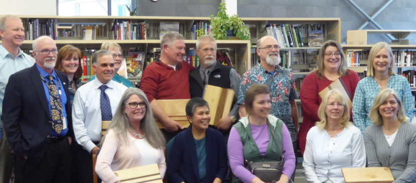 The Juneau School Board poses with a group of retiring teachers and staff members on Tuesday.
