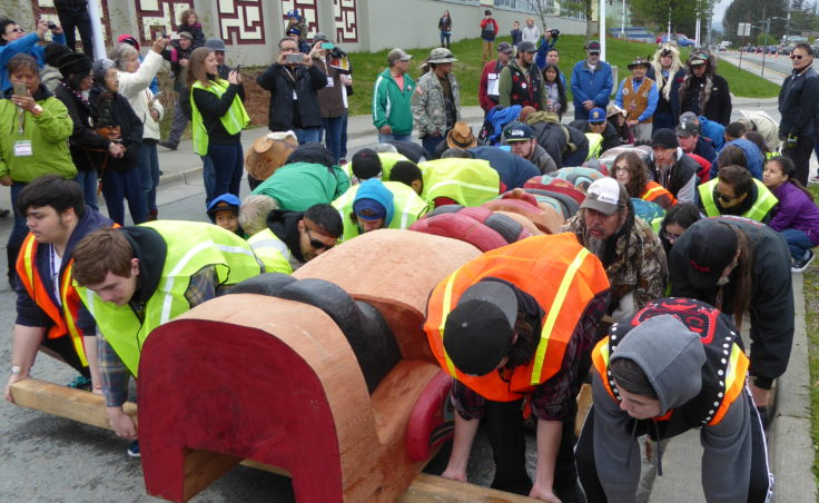 Volunteers lift the Raven totem pole at the totem pole raising in front of Gastineau Elementary School on Saturday.