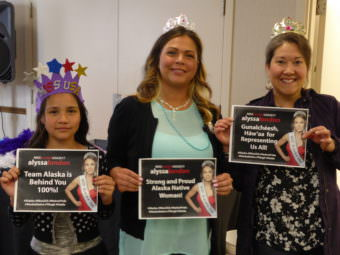 Sierra Flores, left, her mother Serena Hinchman, middle, and Raeanne Holmes hold signs at the Miss USA watch party in the Elizabeth Peratrovich Hall in Juneau on Sunday, May 14, 2017.