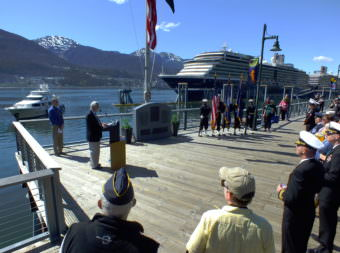 Juneau Mayor Ken Koelsch (at podium) speaks during a memorial service for USS Juneau on the downtown waterfront on Tuesday, May 16, 2017. Juneau Port Director Carl Uchytil listens at far left.