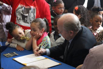 Gov. Bill Walker signs the first half of his name on SB 46 on Sunday at Shiolh Baptist Church in Anchorage, (Photo by Wesley Early/Alaska Public Media)