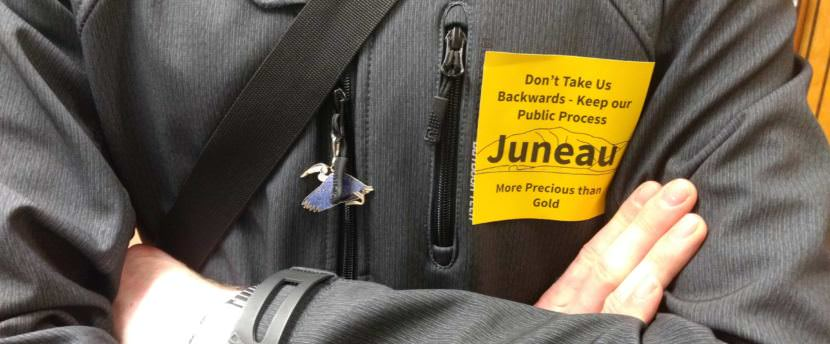 Residents against changing the city's mining ordinance wore yellow stickers to express their opposition at the June 12, 2017, Juneau Assembly meeting. (Photo by Jacob Resneck/KTOO)