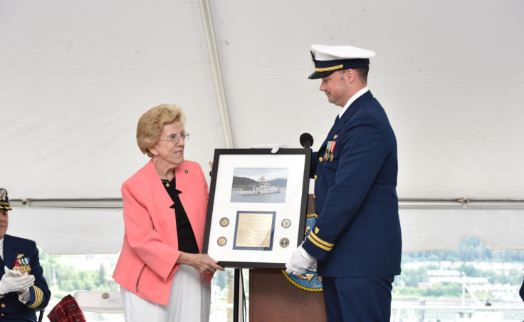 Carol Pugh, sponsor of the Coast Guard Cutter Bailey Barco, receives a commemorative photo of the vessel from Lt. Frank Reed, commanding officer of the cutter Bailey Barco during the vessel's commissioning ceremony in Juneau on June 14, 2017. Pugh is the great granddaughter of the vessel's namesake, Coast Guard hero and Gold Lifesaving Medal recipient Bailey Barco.