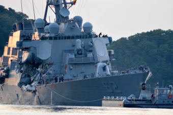 "The guided missile destroyer USS Fitzgerald returns to Yokosuka, Japan, after its collision Saturday. Authorities say the ship's flooding ""has been stabilized,"" but seven sailors remain unaccounted for."