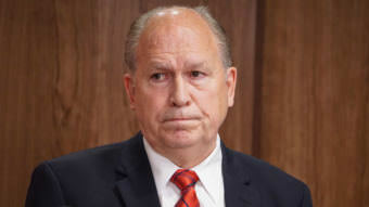 Alaska Gov. Bill Walker listens as Department of Revenue Commissioner Randall Hoffbeck discusses a compromise budget package with reporters in the cabinet room of the Capitol in Juneau on June 6, 2017.