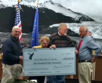 Whale Committee members Jim Clark, left, Jean Overstreet and Bruce Botelho present an oversize check for $250,000 to Mayor Ken Koelsch to help fund the infrastructure for the whale statue at the June 5, 2017 meeting of the Juneau Assembly. (Photo by Jacob Resneck/KTOO)