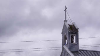 A cross tops the steeple of the Catholic Cathedral of the Nativity of the Blessed Virgin Mary in downtown Juneau on July 15, 2017. (Photo by Jeremy Hsieh/KTOO)