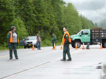 Forest Service employees stand ready to turn visitors away from the Mendenhall Glacier Recreation Center on Sunday.