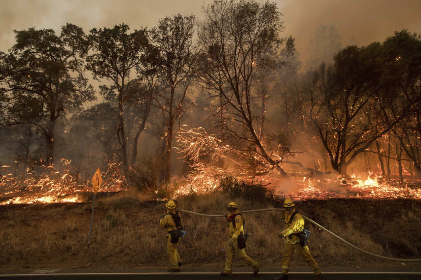 Firefighters try to keep a wildfire from jumping a street near Oroville, Calif., on Saturday. Evening winds drove the fire through several neighborhoods, leveling homes in its path.