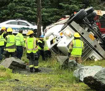 Authorities look over a cement truck that rolled over near the intersection of Mendenhall Loop and Back Loop roads on the morning of July 11, 2017.