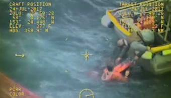 Captain with crewman in water in the process of helping man onto vessel. Screencap from video by Air Station Kodiak
