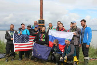 The Russian team and the Dillingham residents who helped to place the monument at Nushagak pose with the American, Russian, and Alaskan flags. (Photo by Allison Mollenkam/KDLG)
