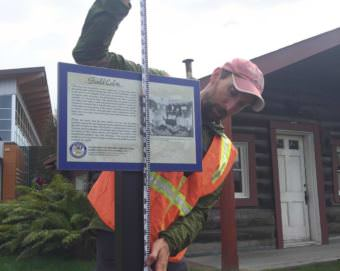 National Weather Service hydrologist Ed Plumb takes a measurement for installation of high water mark sign on an historic cabin near the Morris Thompson Center. (Photo by Dan Bross/KUAC)