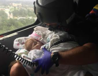 A Coast Guard aircrew assists an infant during the aftermath of Hurricane Harvey in the greater Houston Metro Area Aug. 29, 2017. The Coast Guard has pulled assets and resources from across the country to create a sustainable response force. (USCG photo by Petty Officer 2nd Class Chase Redditt.)