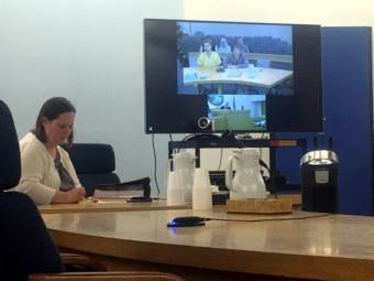 Defendant Reuben Yerkes, dressed in yellow scrubs, appeared in Sitka court via teleconference. He is displayed on a TV screen in the courtroom. Assistant district attorney Amanda Browning appeared in person.