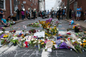Television crews roll with a memorial to Heather Heyer as a backdrop in Charlottesville on Aug. 14, 2017. Heyer was killed counterprotesting a white nationalist rally.