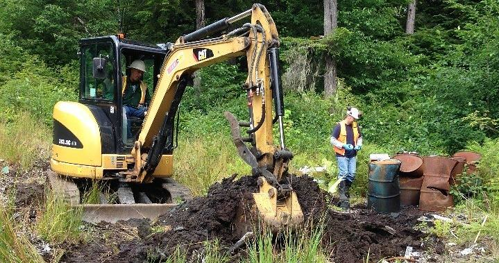 A backhoe digs up part of the old Byford Junkyard in Wrangell in 2014. After removing old cars, oil drums and other trash, the state is treating and moving contaminated soil to a rock quarry south of town. (Photo courtesy Department of Environmental Conservation)