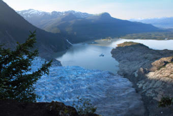 The morning sunlight approaches Mendenhall Glacier across Mendenhall Lake, as seen from Mount McGinnis on Aug. 14, 2012. Many hikers get lost and stranded trying to reach the glacier's ice caves below.