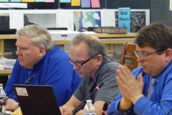 Sean O'Brien sits between Emil Mackey and Dan DeBartolo during a school board meeting in the Thunder Mountain High School Library.