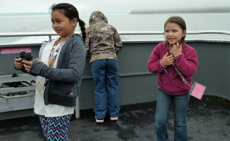 Children play on the back deck of the catamaran St. Peter during the tour of T'aaḵu Kwáan territory. (Photo by Ed Schoenfeld/CoastAlaska News)