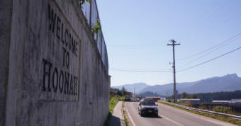 """Motorists drive past a """"Welcome to Hoonah"""" sign on Aug. 6, 2017."""