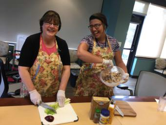 Marcia Anderson, left, and Karolyn Ceron demonstrate how to make fruity salmon salad at the Alaska Native Tribal Health Consortium. (Photo by Anne Hillman/Alaska Public Media)