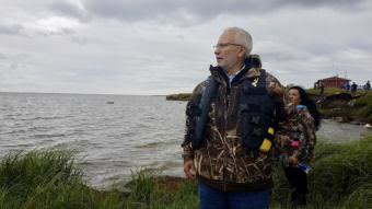 Carlton Kuhns, Assistant Superintendent to the Lower Kuskokwim School District, walks along a debris strewn shoreline of Newtok to the boats headed for Mertarvik. (Photo by Christine Trudeau/KYUK)