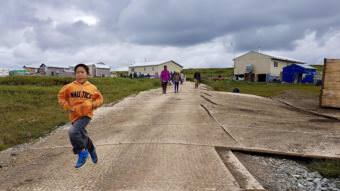 Excited Newtok children sprint down to Mertarvik's newly extended boat harbor. (Photo by Christine Trudeau/KYUK)