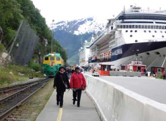 Tourists walk on Skagway's railroad dock in summer of 2016. The cliff, where a rockslide occurred Aug. 26, is adjacent to Skagway's biggest cruise ship dock. (Photo by Emily Files/KHNS)