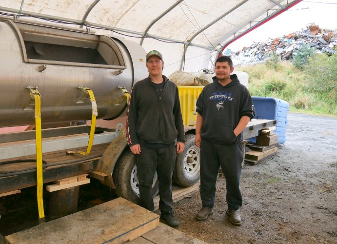 Brandon Thynes, Petersburg Indian Association's Tribal Resource director, and his assistant Clifton Gudgel stand next to the tribe's new composting machine, which is housed in a portable building at the Petersburg Borough's baler facility. (Photo by Angela Denning/KFSK)