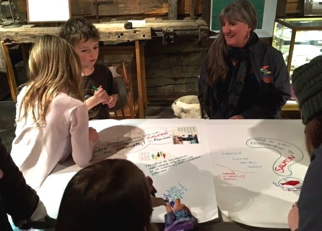 Kitty Farnham, right, watches children write responses to fisheries-based questions. (Photo by Kayla Desroches/KMXT)