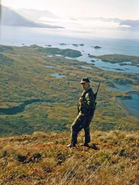 "Calvin Fair stands high on ""Buck Mountain"" north of his group's hunting camp in a public-use cabin in Chief Cove, which can be seen behind Fair in this October 1986 image. (Photo courtesy Clark Fair)"