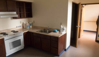 A small kitchenette in the corner of an apartment with a full sized refrigerator, oven, and sink