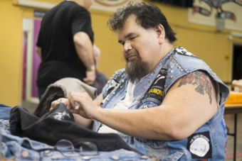 Alfie Price of Juneau sews patches and to a denim vest at Artists of All Nations on Sunday, Sep. 24, 2017. (Photo by Annie Bartholomew/KTOO)