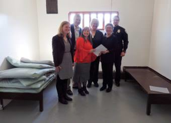 Heather Parker with Gov. Walker's office, DOC Commissioner Dean Williams, Pretrial Director Geri Fox, Haines Mayor Jan Hill, Haines Borough Manager Debra Schnabel and Haines Police Chief Heath Scott pose in a Haines jail cell with a revised community jails contract. (Photo by Emily Files/KHNS)