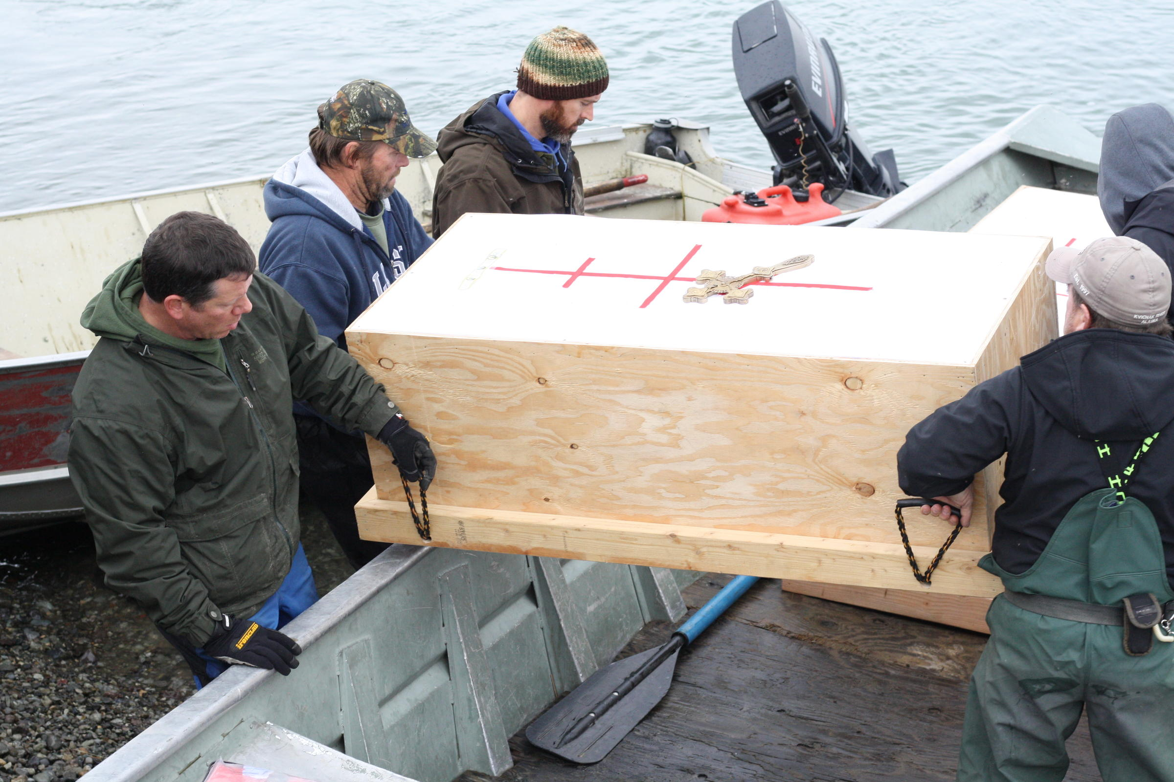 Several people place the coffins in a skiff for the final piece of their journey from Igiuigig to the old village site of Qinuyang. (Photo by Avery Lill/KDLG)