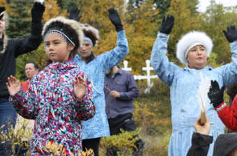 The Igyararmiut, the residents of Igiugig, perform a traditional blessing dance. (Photo by Avery Lill/KDLG)