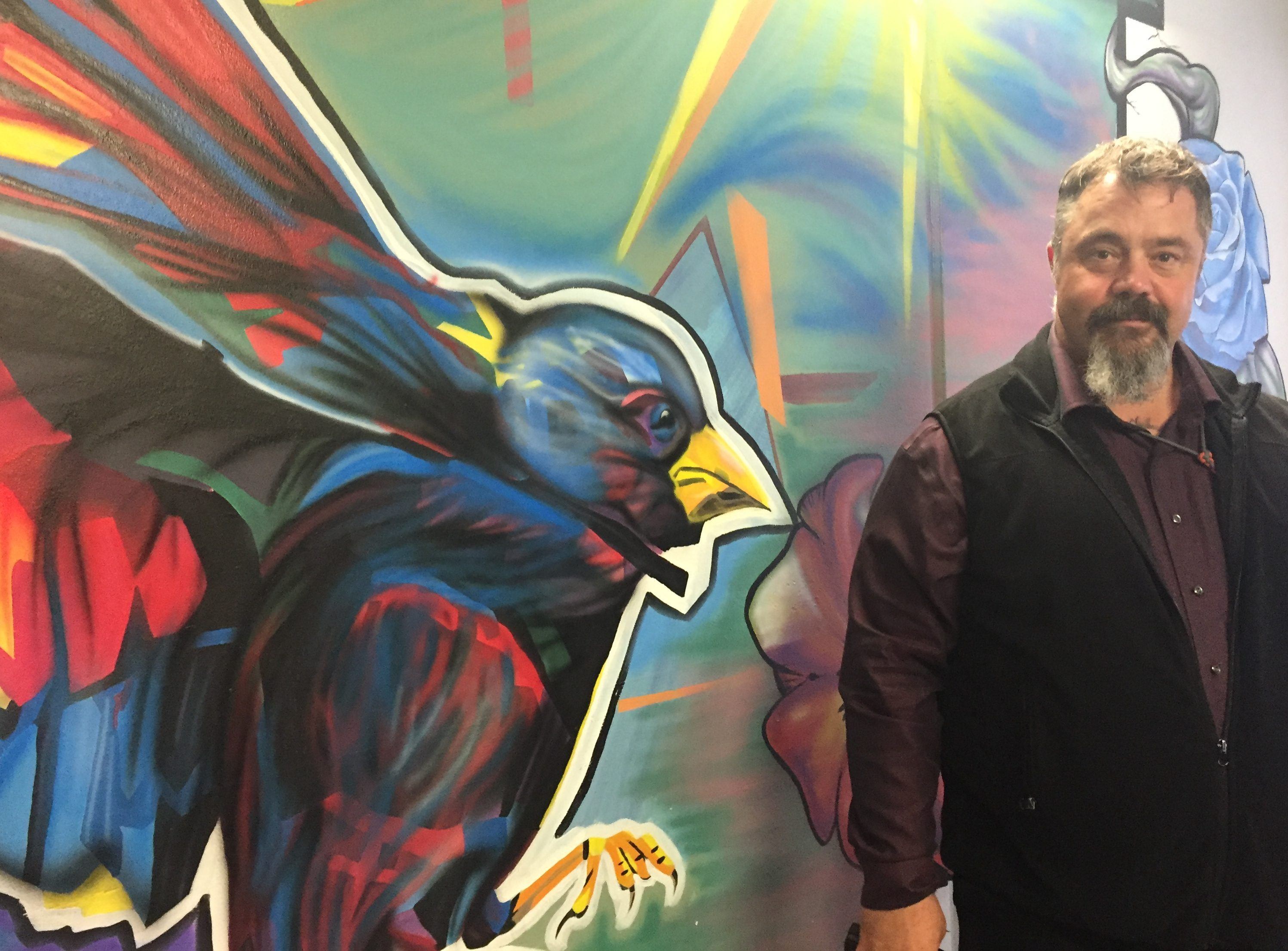Spring Creek Superintendent Bill Lapinskas poses with one of the murals in the segregation housing at the Correctional Center. (Photo by Anne Hillman/Alaska Public Media)