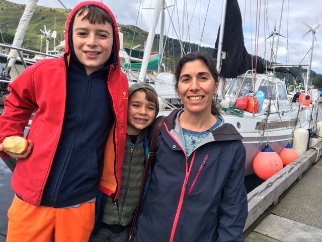 Elias, 11, left, snacks on an apple before going off to a cross country race with his brother Eric, 7, and mom Alisa Abookire. Along with their boys' dad, Mike Litzow, returned to Kodiak after roughly 10 years of sailing the world. (Photo by Kayla Desroches/KMXT)