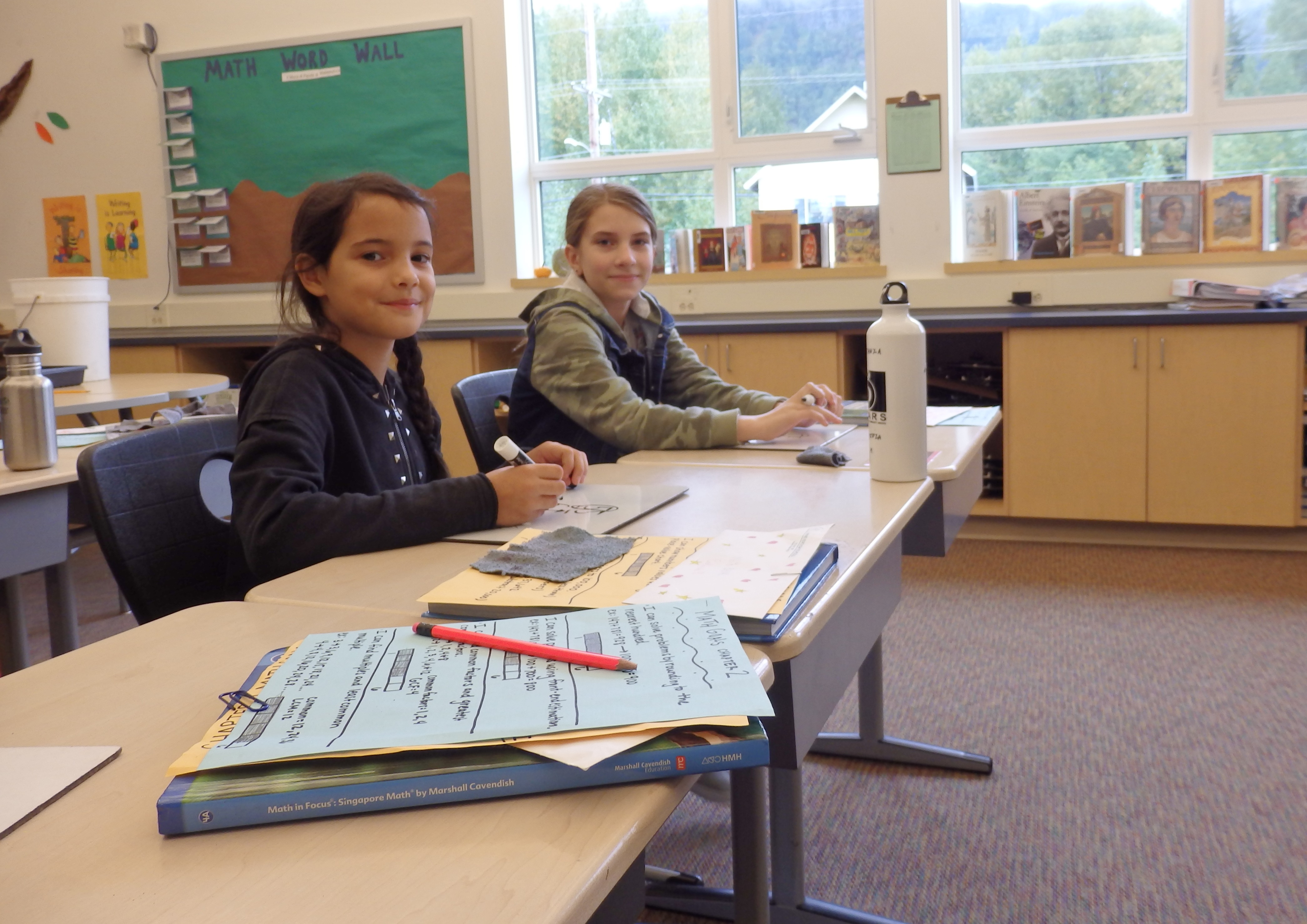 Costanza Marabini, left, went to school in Haines for about a month while visiting a family friend. Marabini sits next to fourth-grader Audrey Bader. (Photo by Emily Files/KHNS)