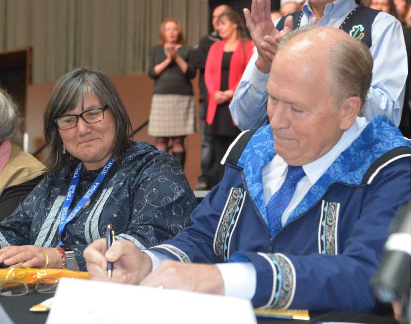 Gov. Bill Walker signs the Alaska Tribal Child Welfare Compact as Health and Social Services Commissioner Valerie Davidson watches at the 2017 Alaska Federation of Natives convention on Wednesday, Oct. 19, 2017.