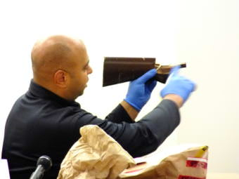 Sgt..Dominic Branson pieces together two pieces of a long gun butt stock that were found in Christopher Strawn's trailer during his homicide trial on Oct. 13, 2017.