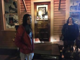 Ghost-tour guide Kelli Klees leads a group to some of Ketchikan's haunted spaces. The Star Building on Creek Street, which houses Soho Coho, is home to a reported ghost. (Photo by Leila Kheiry/KRBD)